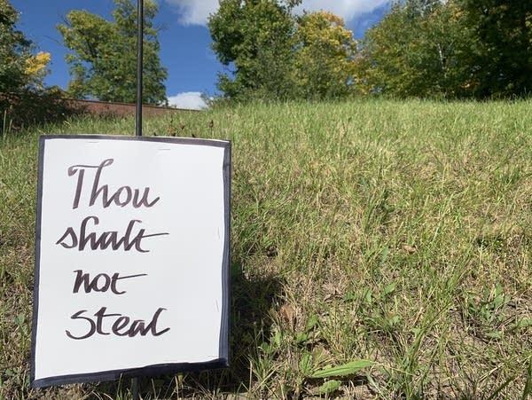 "A hand-made sign reads ""Thou shalt not steal"""