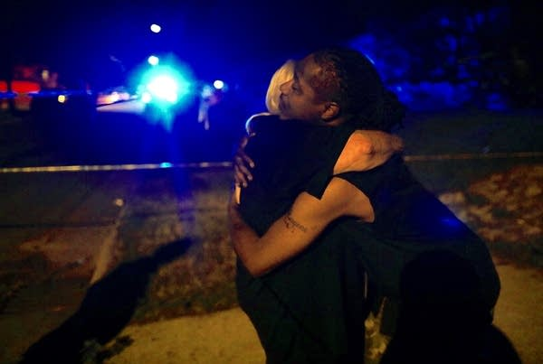 Police chaplain Rev. Linda Koelman hugs Eugene Edwards.