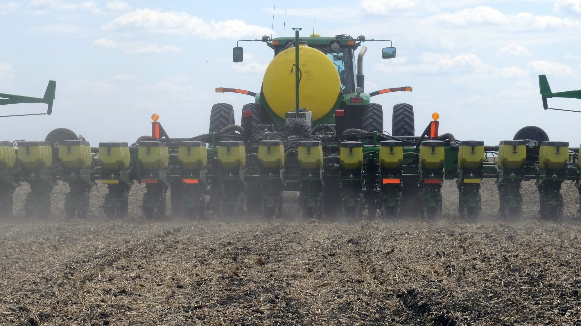 A planter stirs up dust as it buries rows of canola seeds.