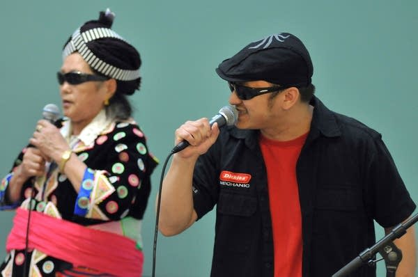 A woman and man hold microphones during a performance.