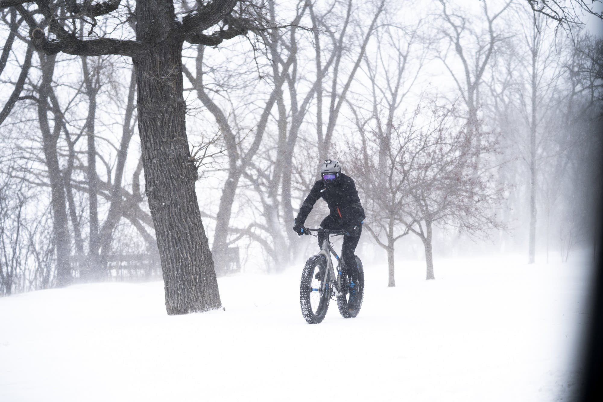 A person rides their fat bike around Lake Harriet during a blizzard.