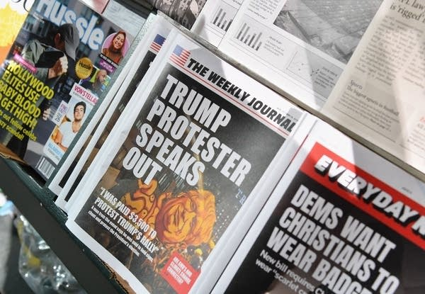 A news stand shows publications with fake headlines.