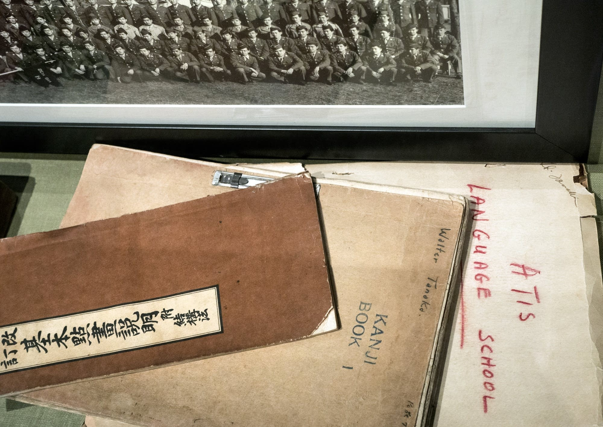 Notebooks from the 1940's are displayed next to a photo.