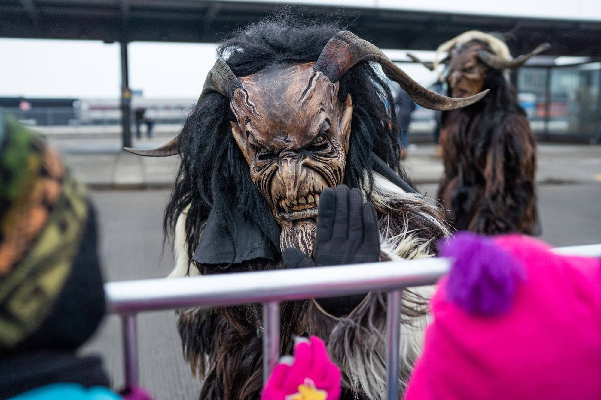 A Krampus waves at children at the Christmas Market.