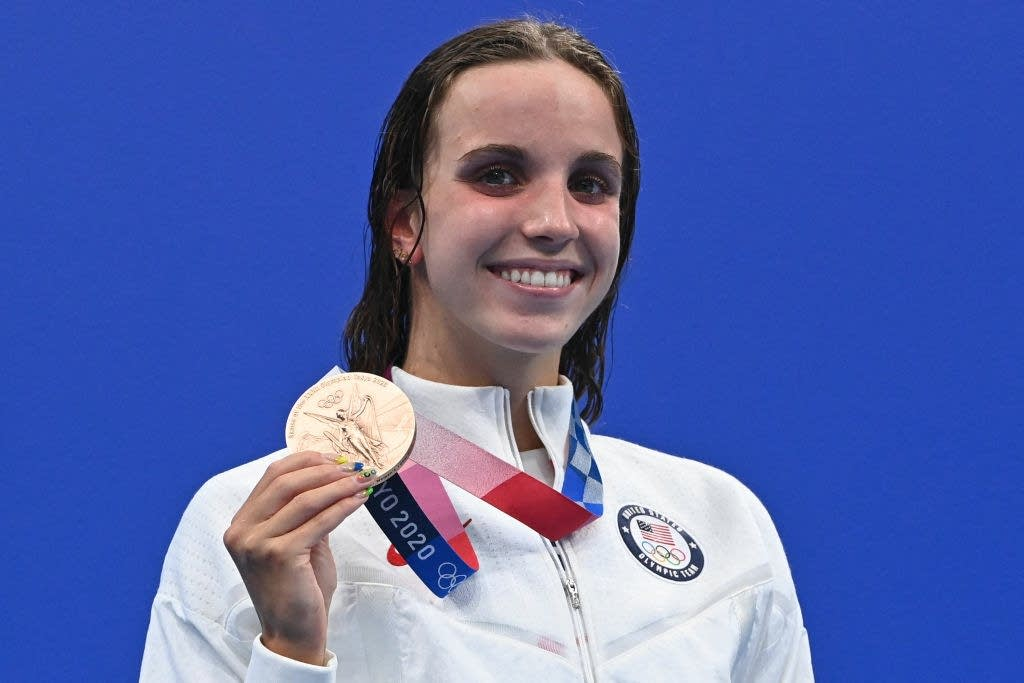 A woman holds her Olympic bronze medal.