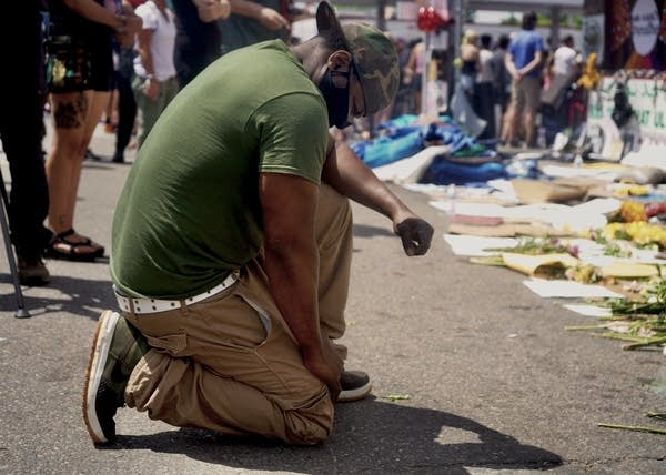 A person kneels in at a memorial.