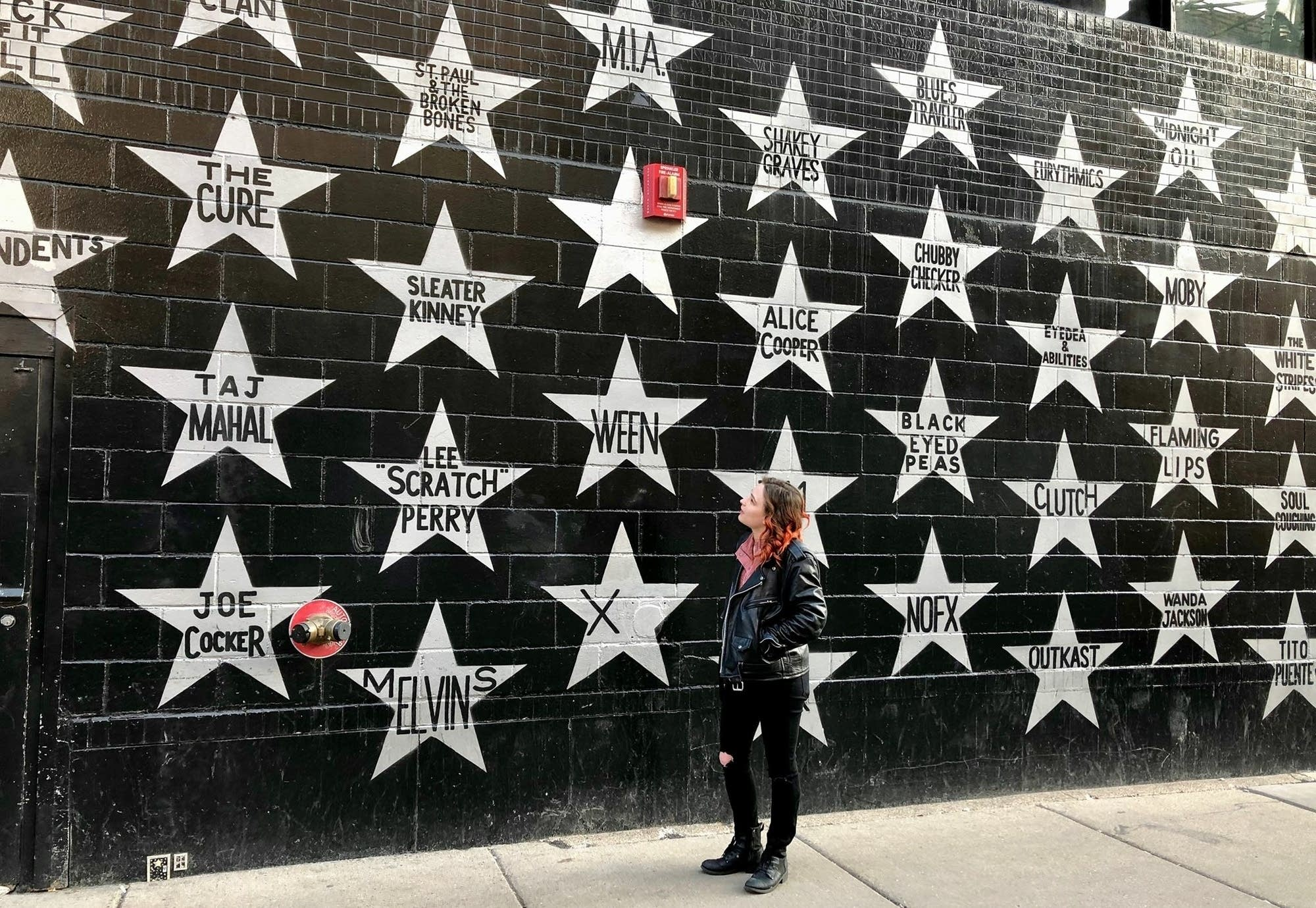 Woman standing in front of First Avenue wall of stars.