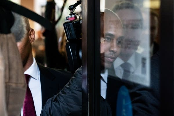 Former Minneapolis police officer Mohamed Noor is reflected in a glass door