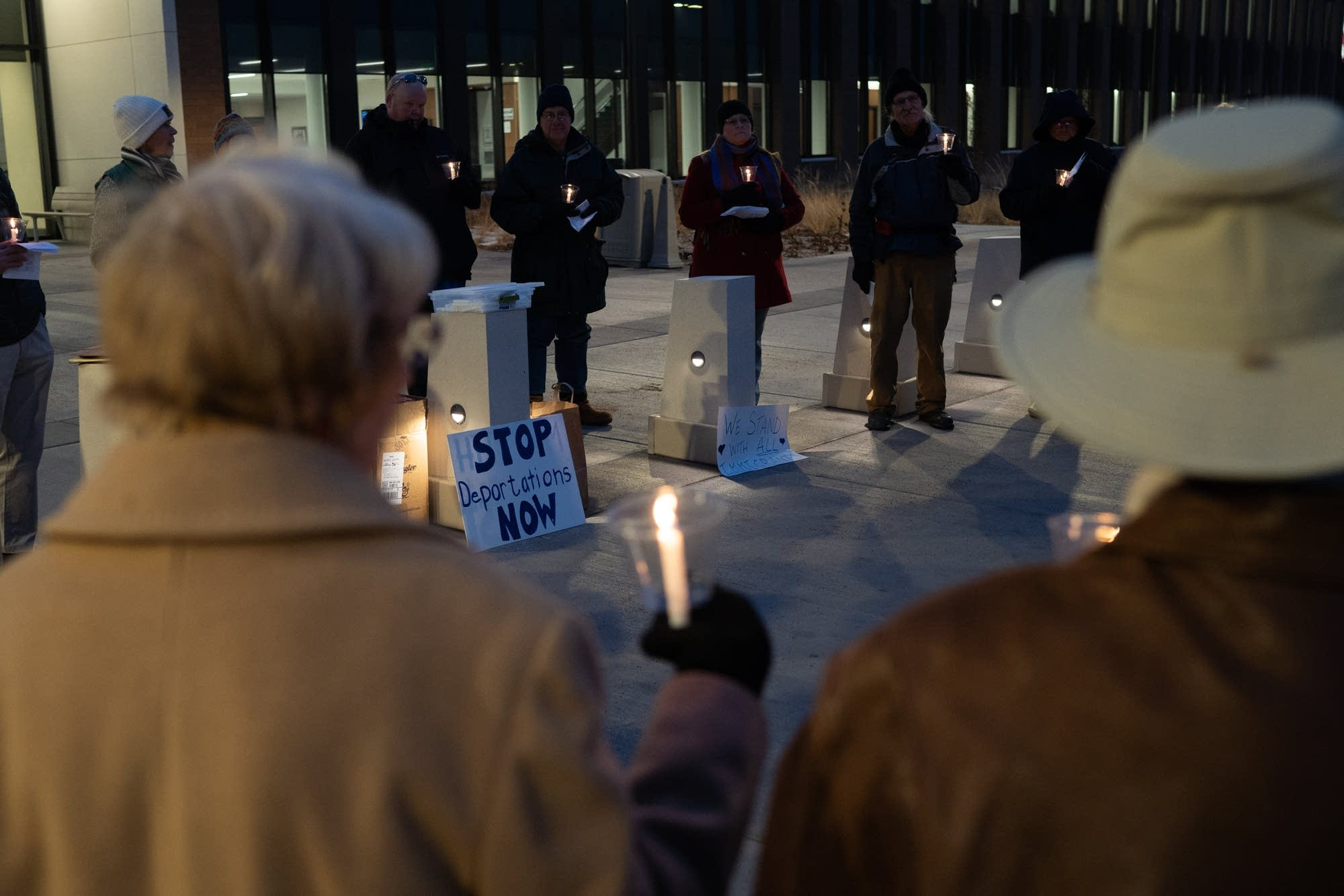 Protesters sing hymns and hold candles outside of the Sherburne County Jail