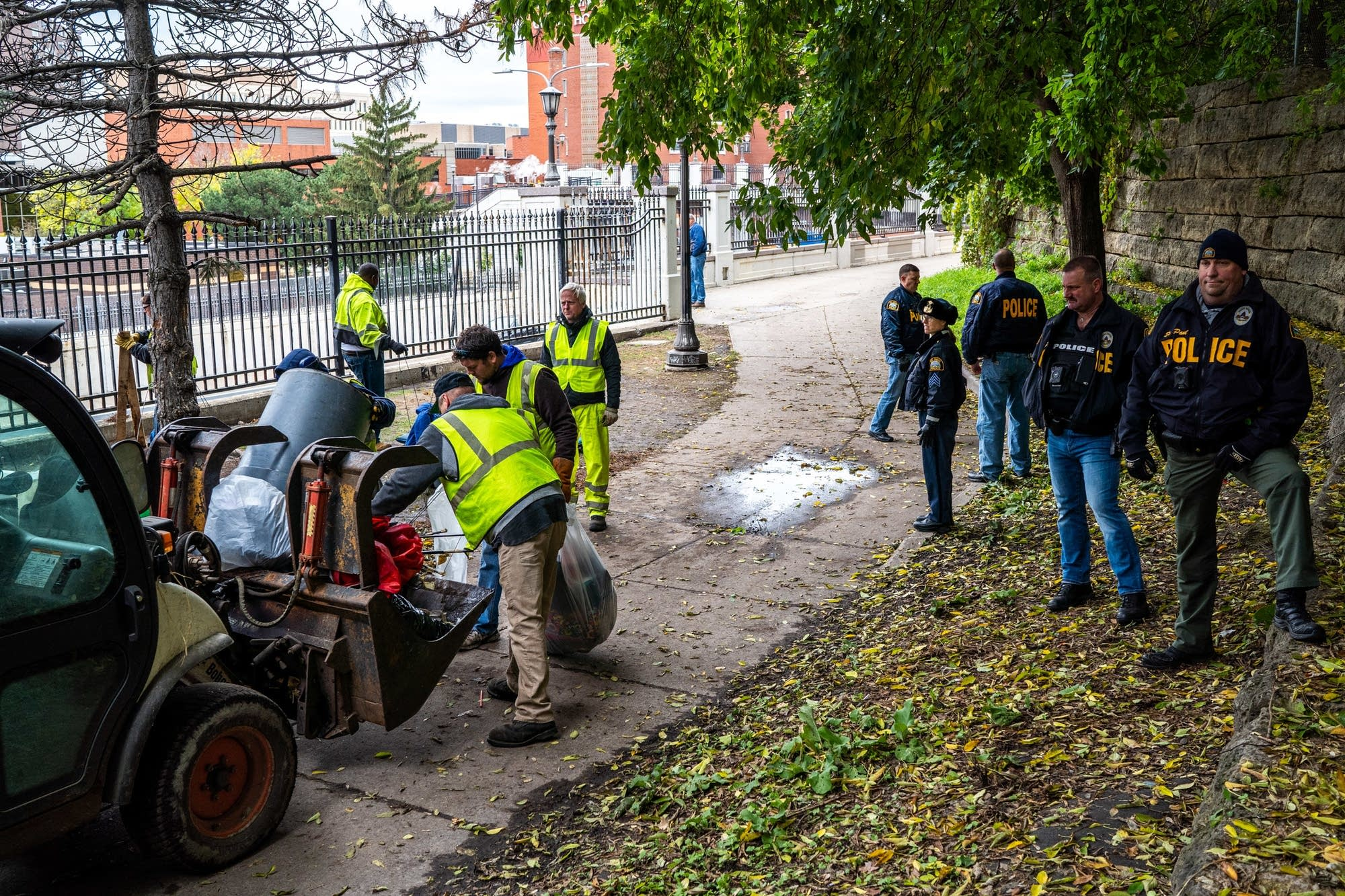 St. Paul police watch as city workers clean up trash.