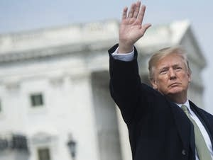 President Donald Trump waves at US Capitol