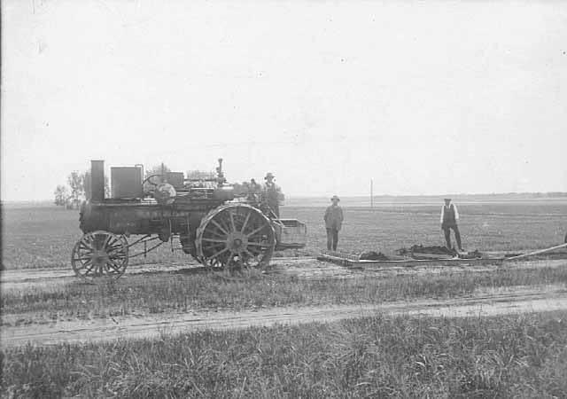 Tractor pulling road grader