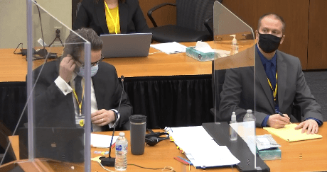A man speaks behind a desk.