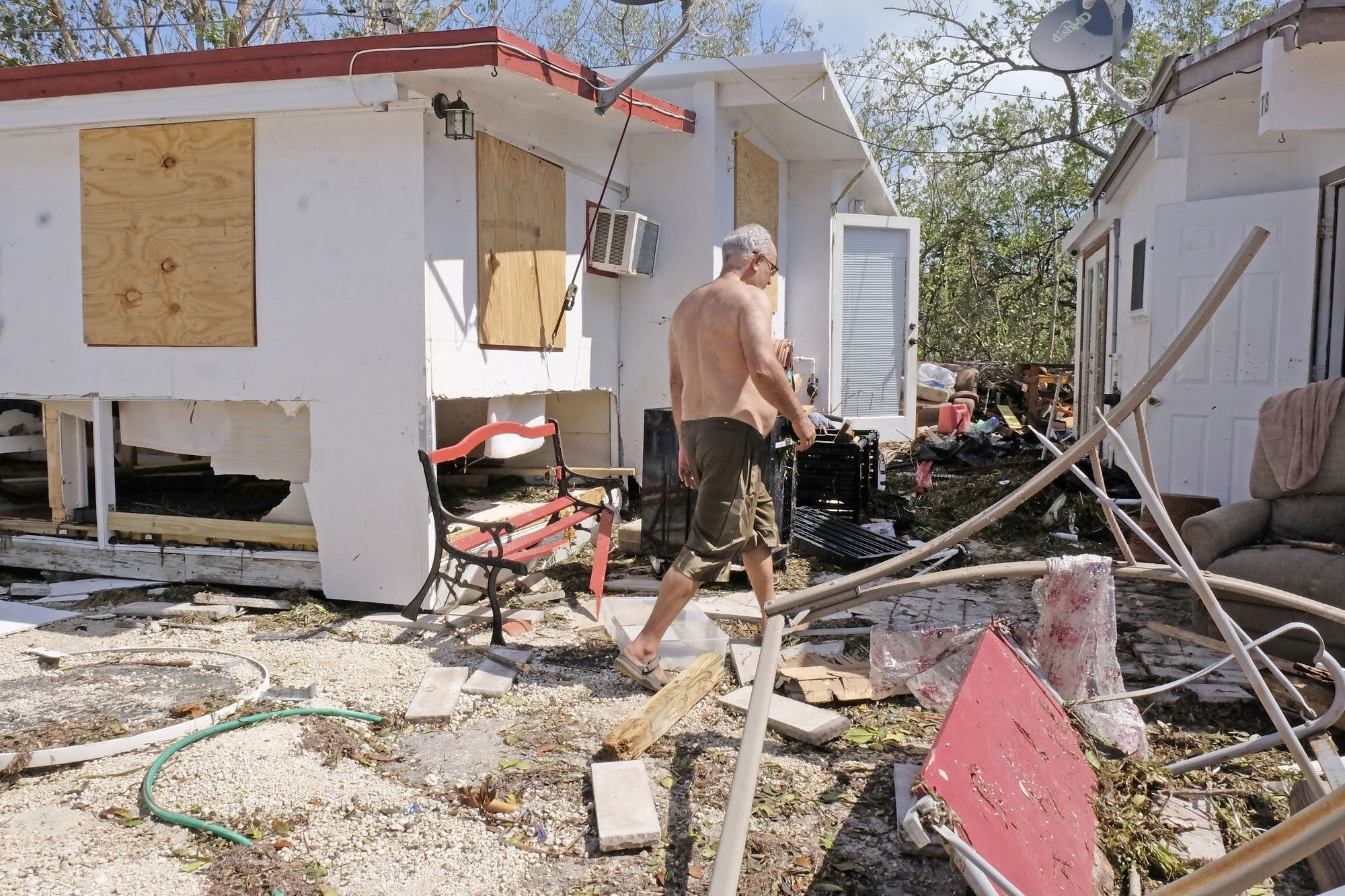 Gullermo Tejera, walks among the damage to his mobile home.
