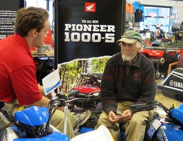Carl Seemann talks with salesman John Frank at Bemidji Sports Center.