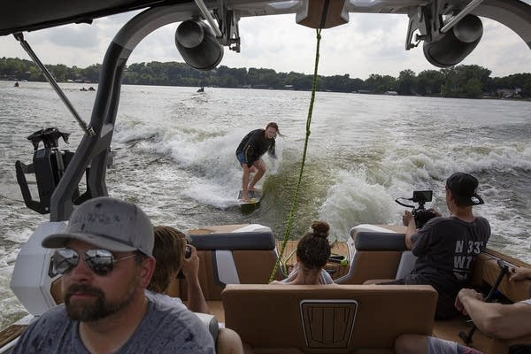 A man wakesurfs behind a boat as passengers watch.