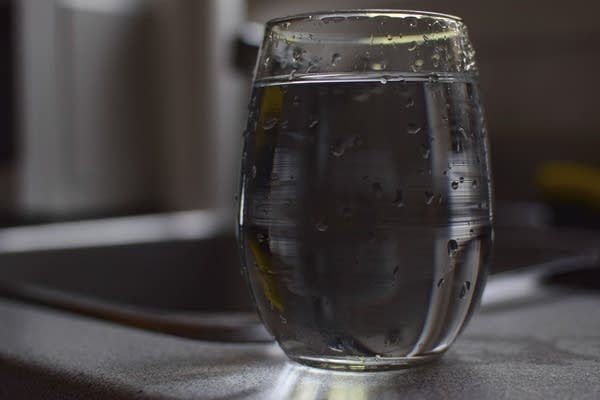 A glass of tap water sits on a counter.
