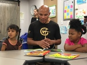Caleb Truax reads to two preschoolers.