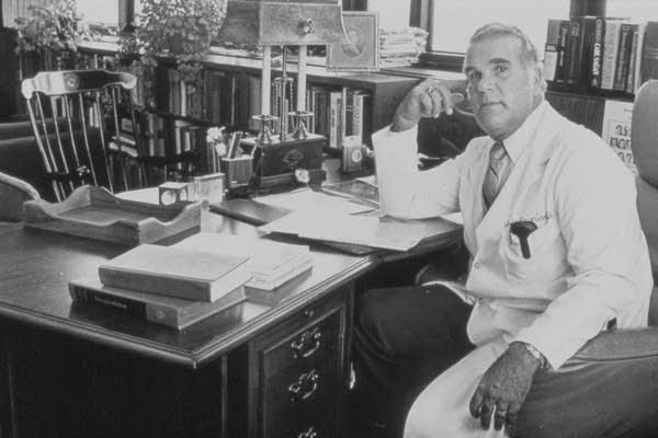 A man sits at his desk.