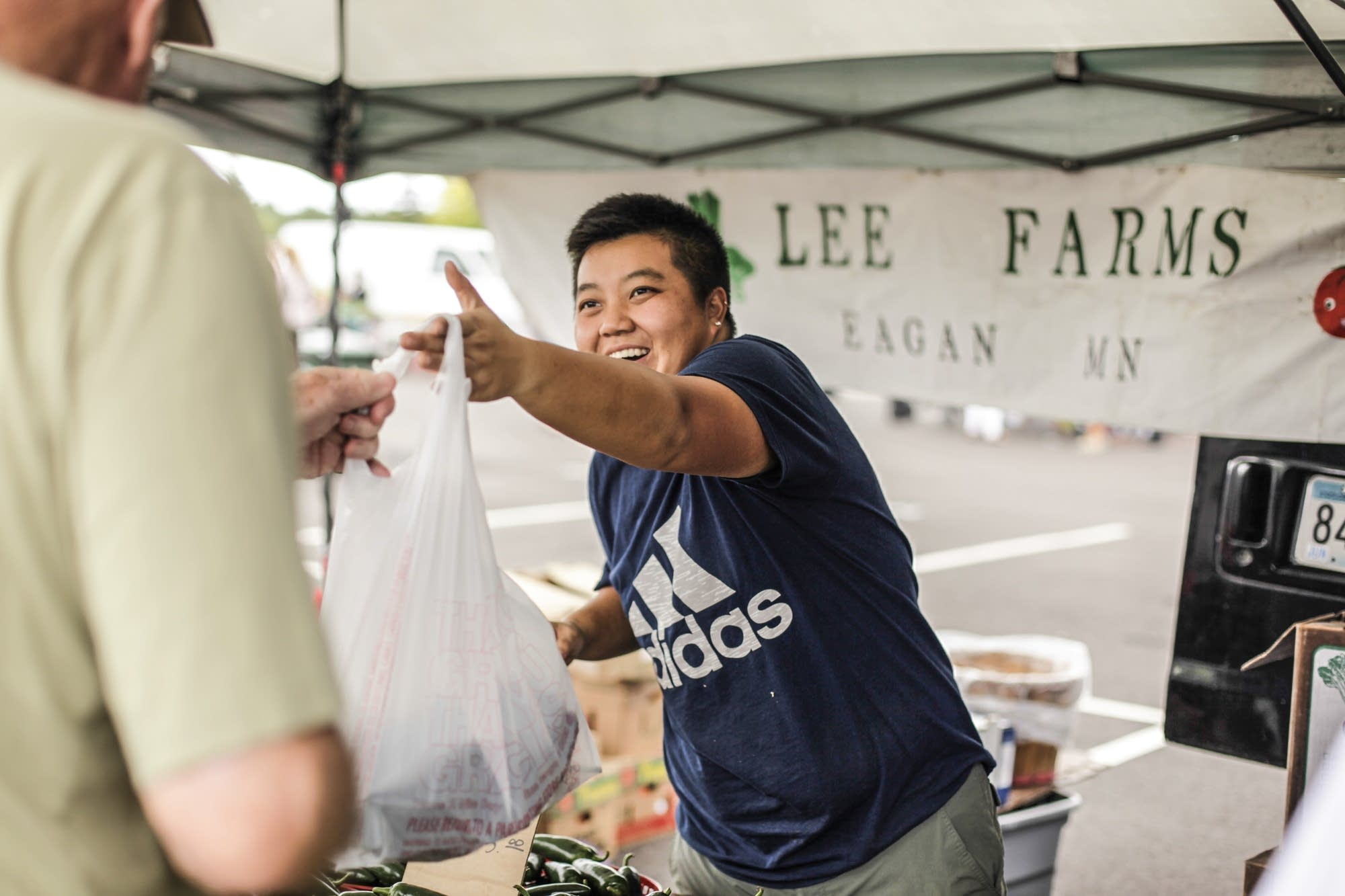 Mao Lee sells produce at the Maple Grove Farmers Market.