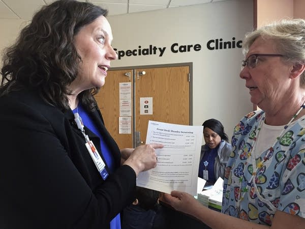 Patsy Stinchfield talks with nurse Kathy Kaul about a measles questionnaire