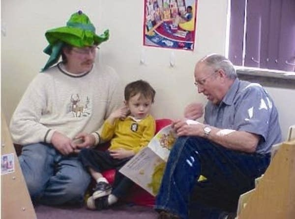 Larry Jones (r) reads to his grandson