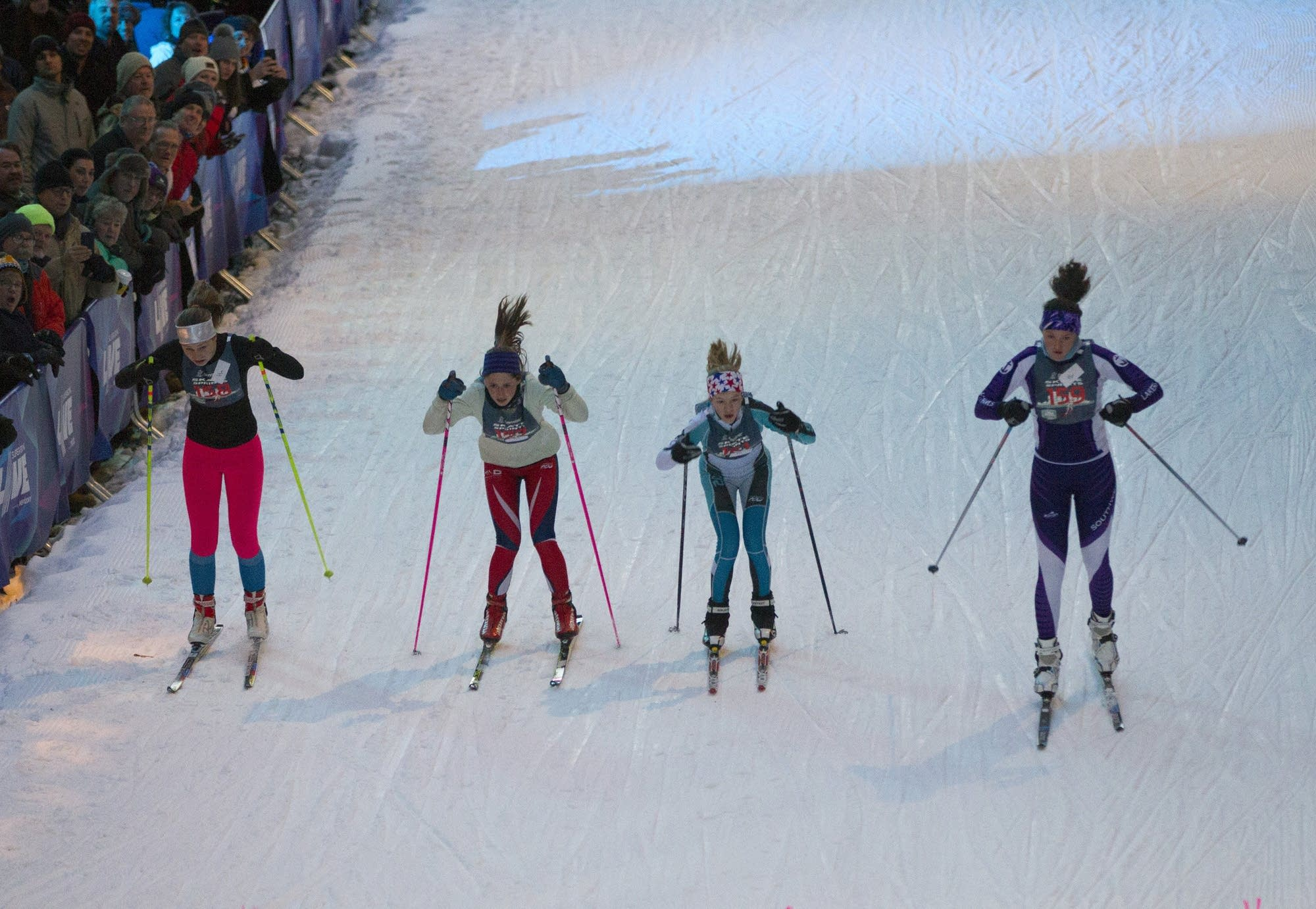 Young nordic skiers rapidly pick up speed at the start of their sprint.