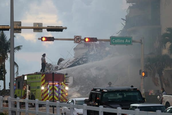 Firefighters spray water on a partially collapsed building.