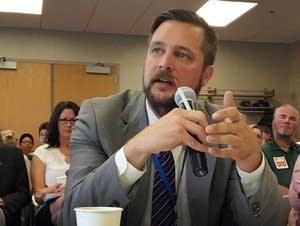 Metropolitan Council chair Adam Duininck, right