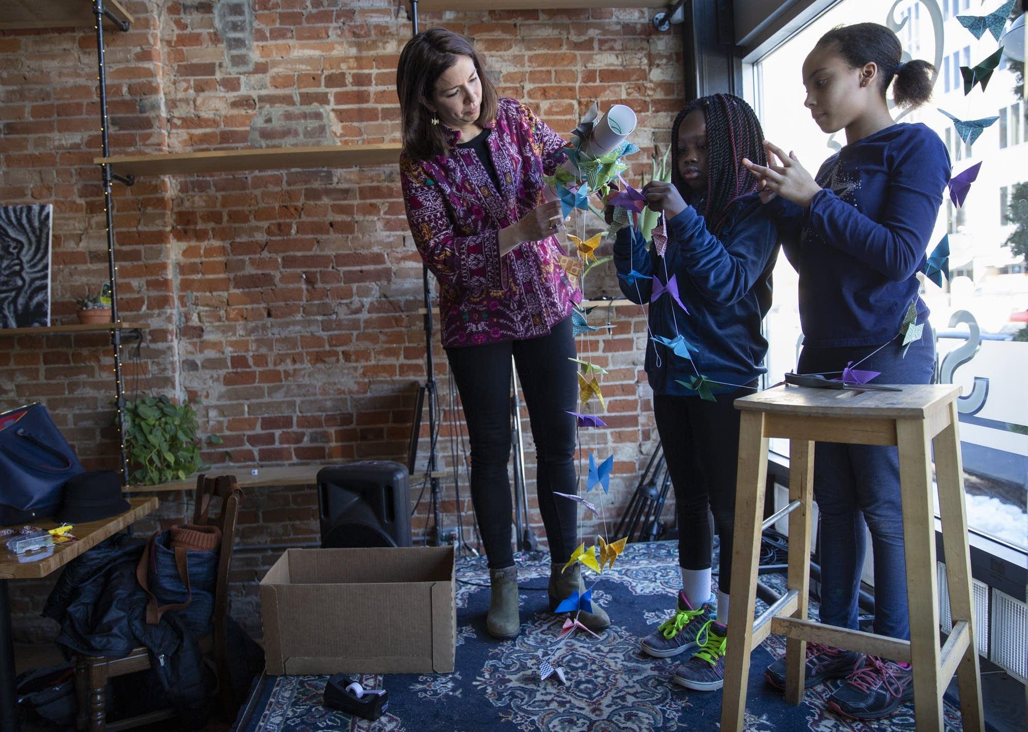 Lida Casper, Lydia Kumbo, 10, and Aliyah Jackson, 11, put up art.