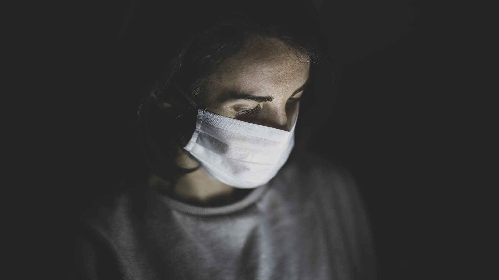 A woman wears a face mask in the dark.
