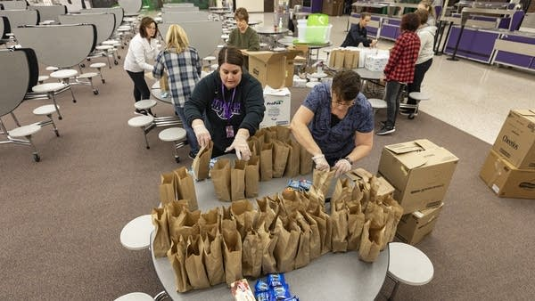 A group of people put food in paper bags.