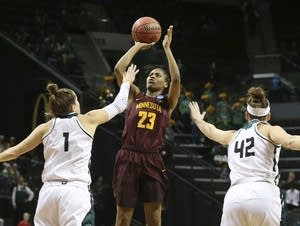 Minnesota's Kenisha Bell, center, shoots
