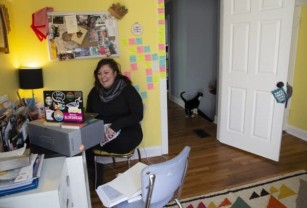 A woman sitting in a home office in front of a laptop