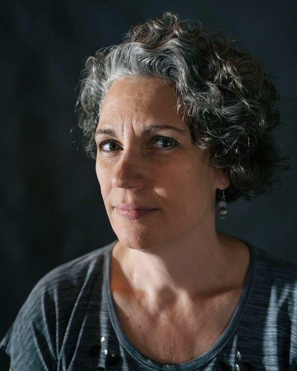 A woman wearing a gray shirt.