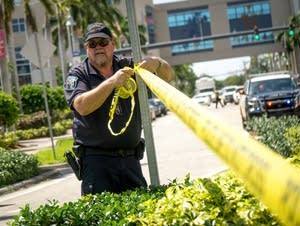 A police officer wraps crime scene tape around a perimeter.