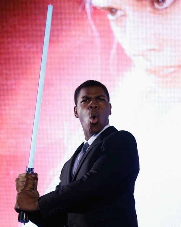 John Boyega poses with a lightsaber