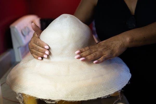 Two hands shape a large white hat.