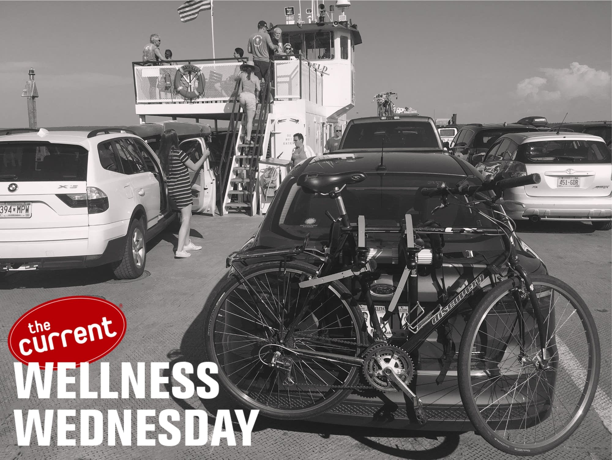 Black and white image of bicycles mounted on a car rack on a ferry.