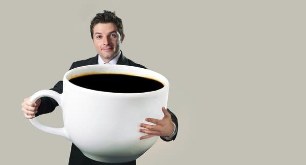 happy businessman holding funny huge oversized cup of black coffee