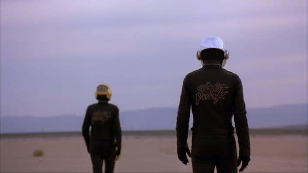 2 people in barren landscape w/ helmets and Daft Punk jackets