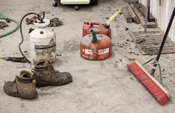 Boots, a broom and gasoline cans are among the items on a concrete floor.