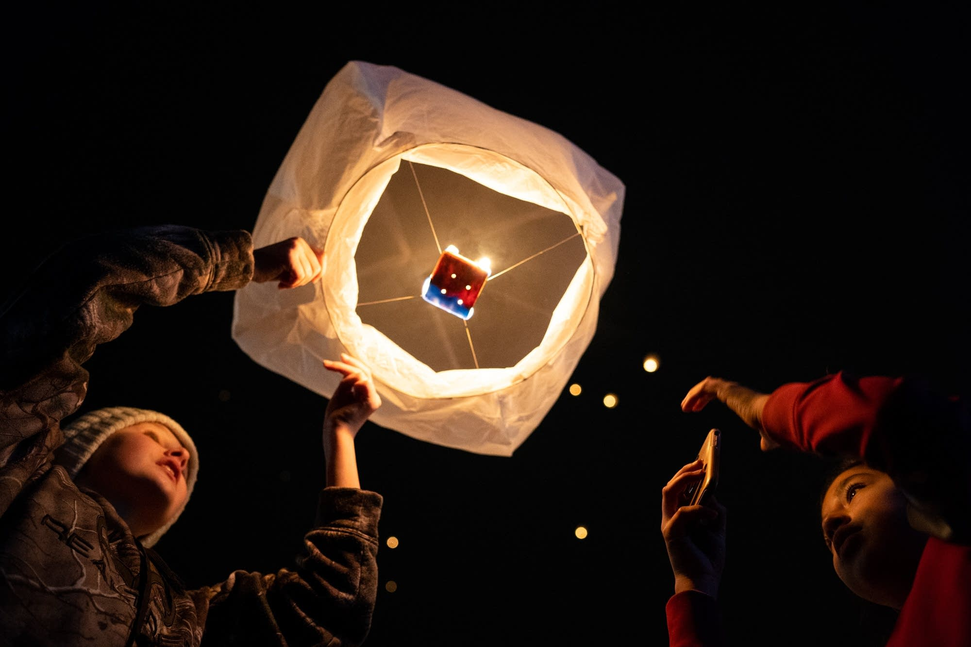 Two Barron, Wis., middle school students light a peace lantern.