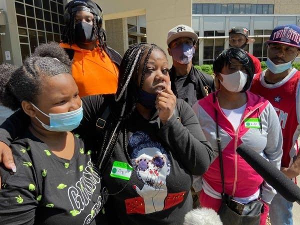 A family, many wearing face masks, gather outside a hospital.