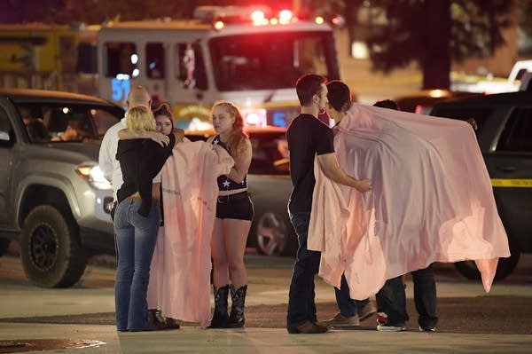 People comfort each other as they stand near the scene of a bar shooting.