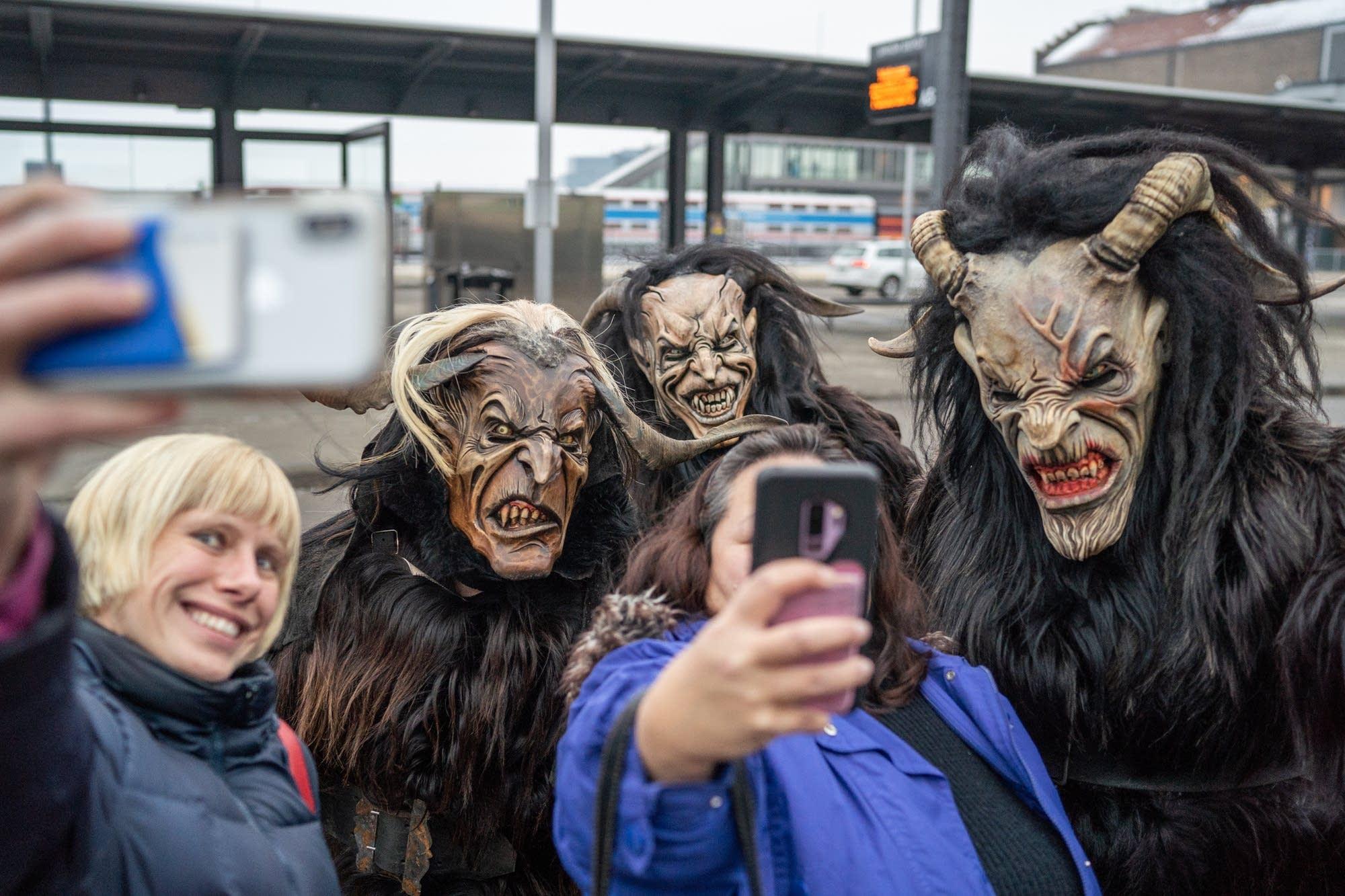 Sasha Denisova and Sheri Arisumi take selfies with three Krampus.