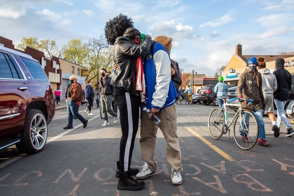 Two people hug in the middle of a street.