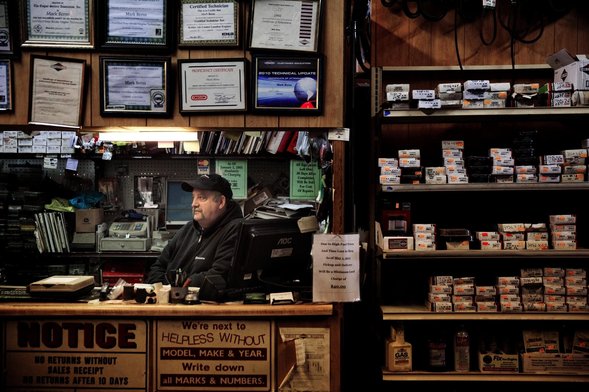 Mark Berns sits in his small engine repair shop