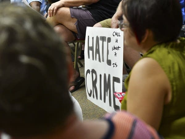 """A hand-painted sign says """"Hate Crime - Call it what it is."""""""