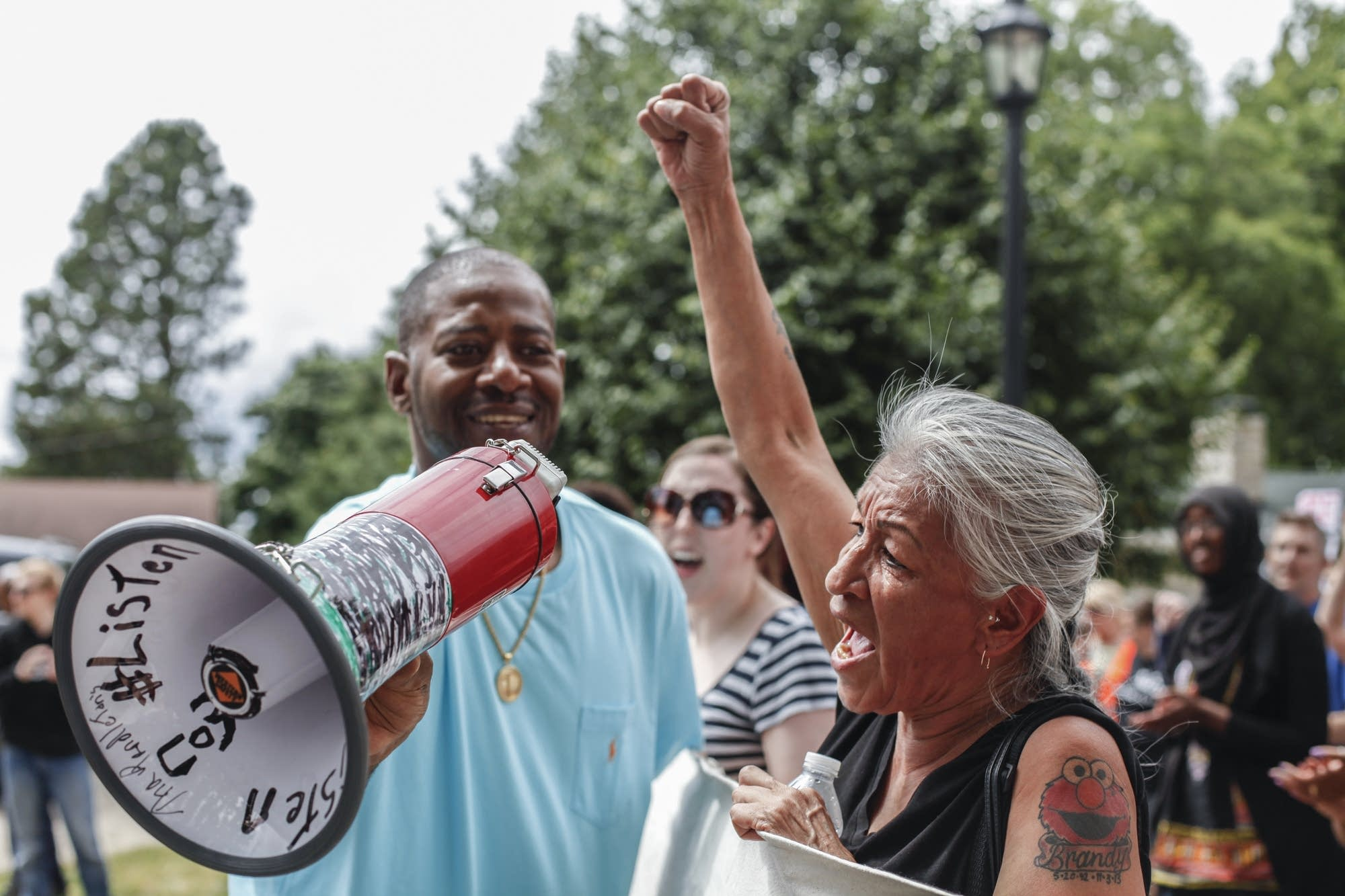 John Thompson passes the megaphone to other protesters.
